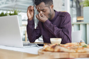 Probably overworked man sitting in front of a laptop
